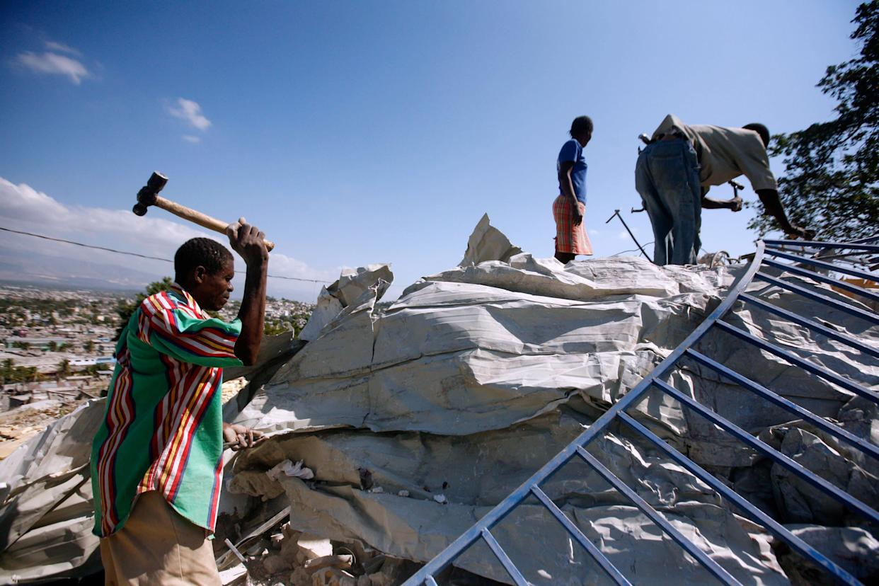 Locals remove building materials at a site in Cite Soleil, Port-au-Prince, on Feb. 4, 2010.