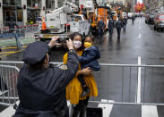 A New York City police officer takes a photo for a passerby as the modified Macy's Thanksgiving Day Parade moves along a few blocks away in the background, in New York, Thursday, Nov. 26, 2020. Due to the pandemic, crowds of onlookers were not allowed to attend the annual parade. (AP Photo/Craig Ruttle)