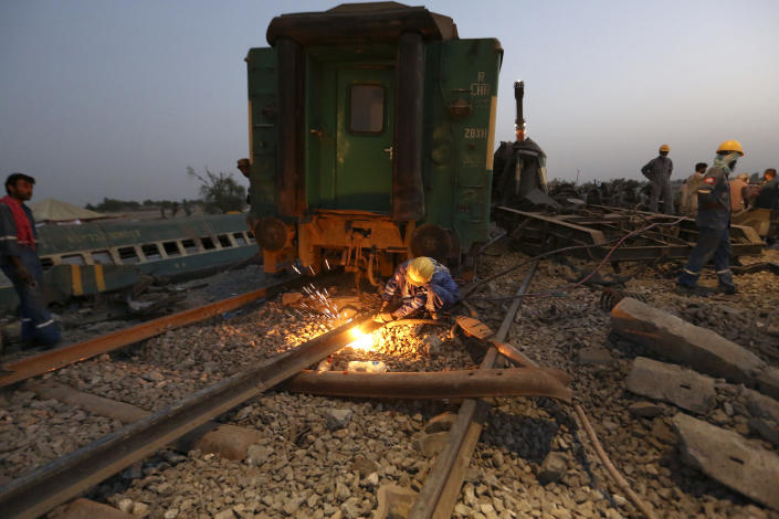 Railway workers rebuild the track at the track at the site of a train collision in the Ghotki district, southern Pakistan, Monday, June 7, 2021. An express train barreled into another that had derailed in Pakistan before dawn Monday, killing dozens of passengers, authorities said. More than 100 were injured, and rescuers and villagers worked throughout the day to search crumpled cars for survivors and the dead. (AP Photo/Fareed Khan)
