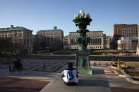 FILE - In this Monday, March 9, 2020 file photo, A woman sits on the Columbia University campus, Monday, March 9, 2020, in New York. Colleges throughout the U.S. are assuring students that this coming fall will bring a return to in-person classes, intramural sports and mostly full dormitories. But those promises come with asterisks. (AP Photo/Mark Lennihan, File)