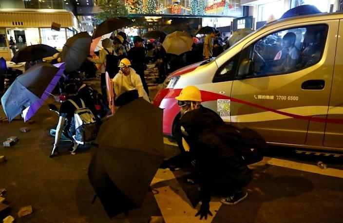 A taxi stops as anti-government demonstrators block a street during a protest at Tsim Sha Tsui, in Hong Kong