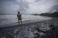 Sri Lankan man, Kindston Jayalath fishes on a polluted beach filled with plastic pellets washed ashore from the fire-damaged container ship MV X-Press Pearl in Kapungoda, on the out skirts of Colombo, Sri Lanka, Friday, June 4, 2021. Authorities were trying to head off a potential environmental disaster as the Singapore flagged ship that had been carrying chemicals was sinking off of the country's main port. (AP Photo/Eranga Jayawardena)