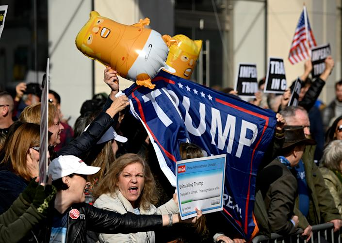 Protestors hold signs during a rally against US President Donald Trump, near the Veterans Day Parade on Nov. 11, at 2019 in New York City. (Photo: Johannes Eisele/AFP via Getty Images)