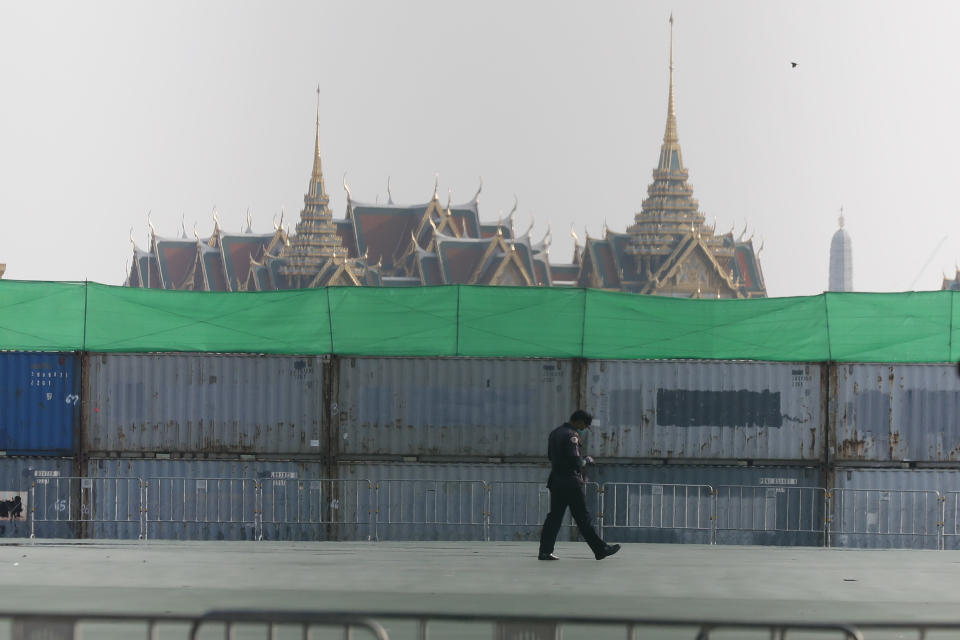 A security officer walks in front of shipping containers used as a barricade in front of the Grand Palace Saturday, March 20, 2021, in Bangkok, Thailand. Thailand's student-led pro-democracy movement is holding a rally in the Thai capital, seeking to press demands that include freedom for their leaders, who are being held without bail on charges of defaming the monarchy. (AP Photo/Sakchai Lalit)