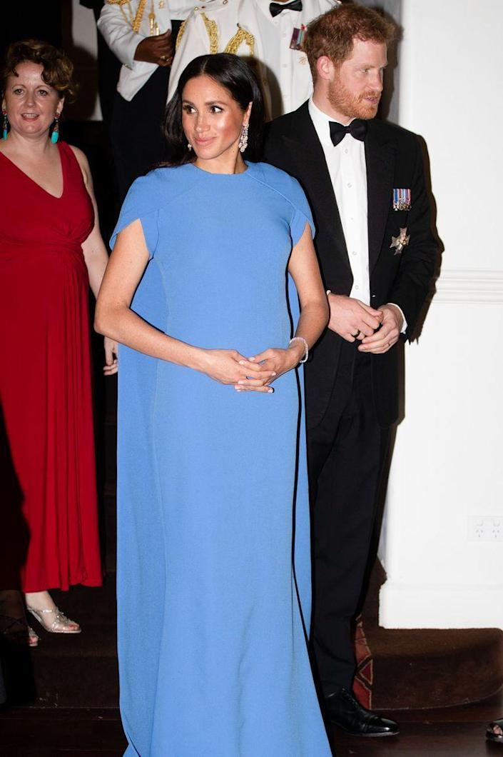 """<p>The newest member of the British royal family looked stunning in a gown by Safiyaa that featured a cape while on a royal visit to Fiji. <a href=""""https://www.townandcountrymag.com/style/fashion-trends/a24106614/meghan-markle-fijian-blue-gown-safiyaa-state-dinner-photos/"""" rel=""""nofollow noopener"""" target=""""_blank"""" data-ylk=""""slk:The vibrant Fijian blue color"""" class=""""link rapid-noclick-resp"""">The vibrant Fijian blue color</a> of the gown was a tribute to the country's flag.</p>"""