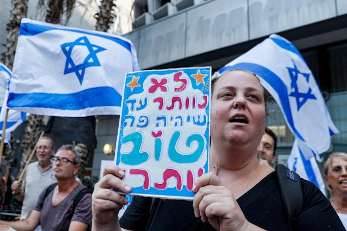 """A supporter of Israel's newly formed government """"change coalition"""" holds a placard reading in Hebrew """"we won't give up until it's better here!"""" during a rally in support of the coalition in Tel Aviv, on June 6, 2021."""