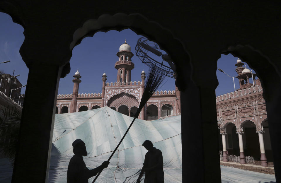 FILE - In this, Friday, April 9, 2021, file photo, volunteers clean the outer areas of the historic Mohabat Khan Mosque ahead of the upcoming Muslim fasting month of Ramadan, in Peshawar, Pakistan. Muslims are facing their second Ramadan in the shadow of the pandemic. Many Muslim majority countries have been hit by an intense new coronavirus wave. While some countries imposed new Ramadan restrictions, concern is high that the month's rituals could stoke a further surge. (AP Photo/Muhammad Sajjad, File)