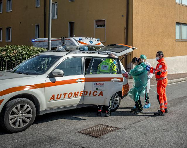 A person suspected to have the coronavirus is helped into an ambulance by medical personnel n Nembro, Italy. (Fotogramma/Abaca via Zuma Press)