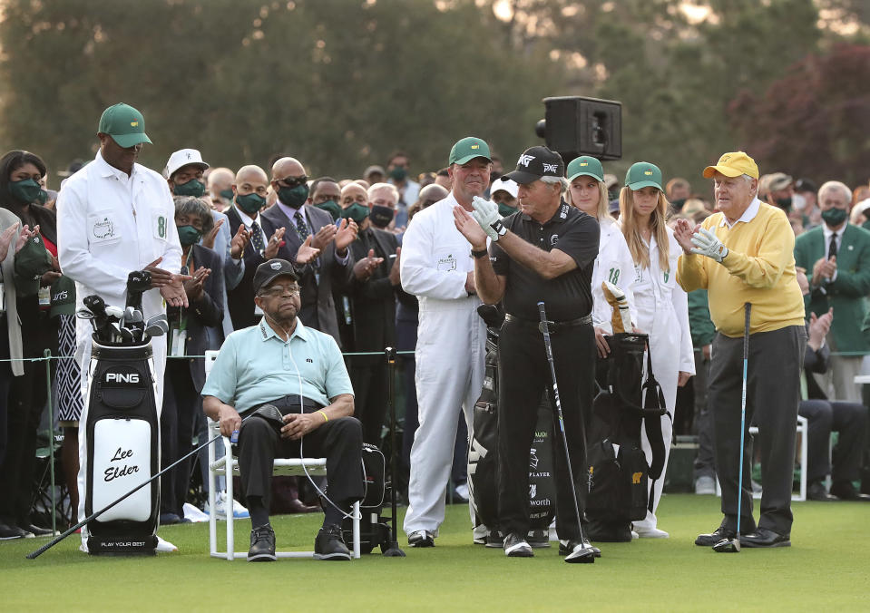 Honorary starter Lee Elder, seated at left, is applauded by three-time Masters champion Gary Player, and six-time Masters champion Jack Nicklaus, right, as he is introduced during the ceremonial tee shots to begin the Masters golf tournament at Augusta National Golf Club in Augusta, Ga., Thursday, April 8, 2021. (Curtis Compton/Atlanta Journal-Constitution via AP)