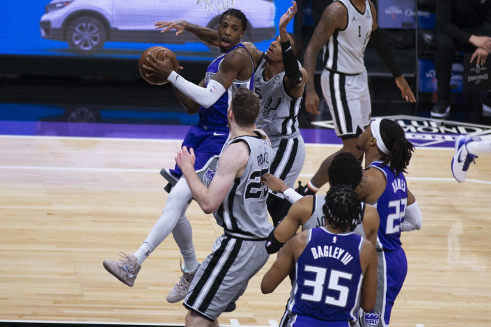 Sacramento Kings guard Delon Wright looks to make a pass as he's defended under the basket by San Antonio Spurs center Jakob Poeltl (25) during the first quarter of an NBA basketball game in Sacramento, Calif., Friday, May 7, 2021. (AP Photo/Hector Amezcua)