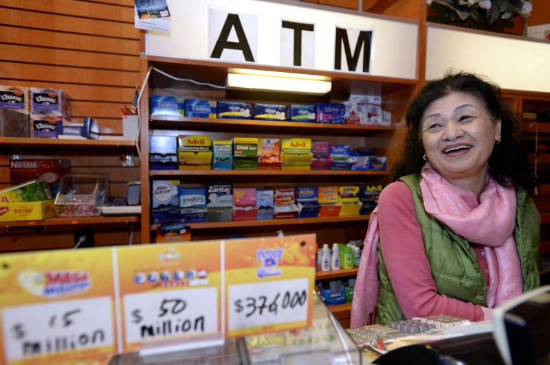 Owner Young Soolee basks in the attention at her small Alliance Center office bulding newsstand on Wednesday, Dec. 18, 2013, in Atlanta, after lottery officials said one of two winning Mega Millions lottery tickets were purchased from her store in Tuesday's $636 million drawing, The store owner said she sold 1300 lottery tickets on Tuesday rather than the normal sales of about 100 tickets. (AP Photo/David Tulis)