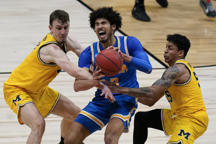 UCLA guard Johnny Juzang is fouled while catching a pass between Michigan guard Franz Wagner, left, and guard Eli Brooks, right, during the second half of an Elite 8 game in the NCAA men's college basketball tournament at Lucas Oil Stadium, Tuesday, March 30, 2021, in Indianapolis. (AP Photo/Michael Conroy)