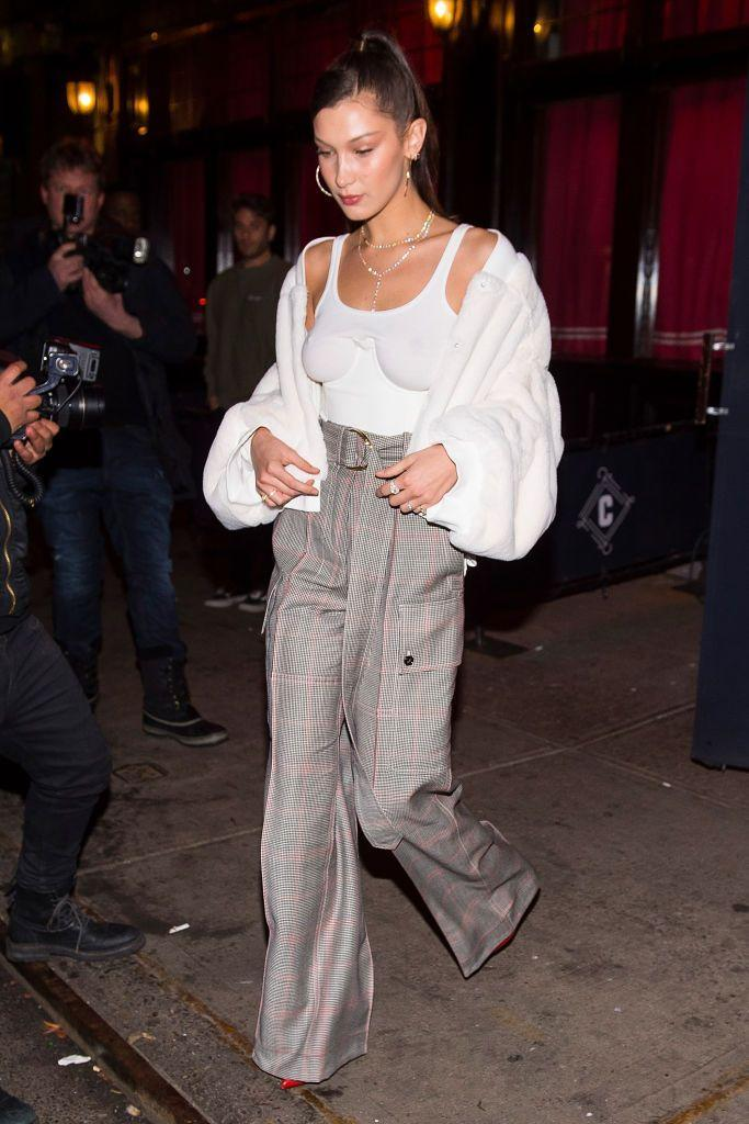 <p>In Greenwich Village, New York City, wearing a see-through white vest top, with high-waisted pants, red boots, and a Jemma Wynne signet ring.</p>