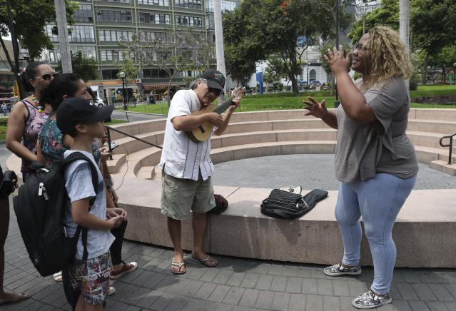 In this Dec. 28, 2018 photo, Venezuelan singer Reymar Perdomo, right, sings with fans who approached her while she was doing a press interview at a park in the Miraflores area of Lima, Peru. According to the International Organization for Migration, more than 3 million Venezuelans have left their country since 2015 as food shortages and hyperinflation became rampant in what was once a wealthy oil-exporting nation. (AP Photo/Martin Mejia)