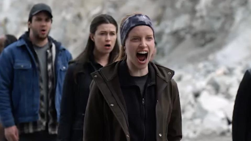 Two women and a man stand outside screaming