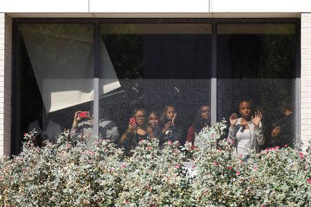 People look out the windows of Confluence Preparatory Academy as protesters march down the street after the not guilty verdict in the murder trial of Jason Stockley, a former St. Louis police officer, charged with the 2011 shooting of Anthony Lamar Smith, who was black, in St. Louis, Missouri, U.S., September 15, 2017. REUTERS/Whitney Curtis