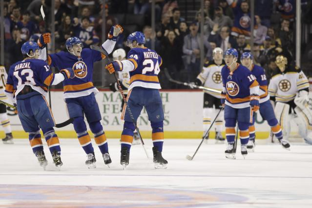 New York Islanders' Scott Mayfield (24) celebrates with teammates Noah Dobson (8) and Mathew Barzal (13) after scoring a goal during the first period of an NHL hockey game against the Boston Bruins, Saturday, Jan. 11, 2020, in New York. (AP Photo/Frank Franklin II)