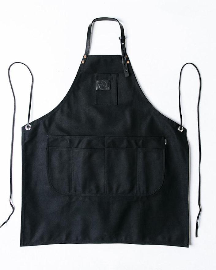 """And speaking of bakers and home chefs, an apron is another go-to housewarming pick that is sure to get ample use. This durable designer apron is made from leather and canvas. $185, Mi Cocina. <a href=""""https://micocinaus.com/products/apron-ap-1-black-canvas-leather"""" rel=""""nofollow noopener"""" target=""""_blank"""" data-ylk=""""slk:Get it now!"""" class=""""link rapid-noclick-resp"""">Get it now!</a>"""