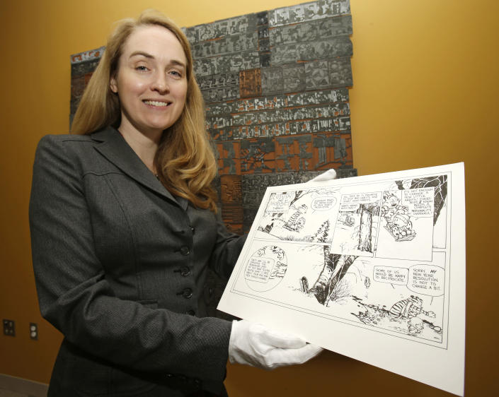 """In this Wednesday, Oct. 23, 2013 photo, Juli Slemmons holds a """"Calvin and Hobbes"""" comic by cartoonist Bill Watterson at the Billy Ireland Cartoon Library & Museum in Columbus, Ohio. Today the museum collection includes more than 300,000 original strips from everybody who's anybody in the newspaper comics world, plus 45,000 books, 29,000 comic books and 2,400 boxes of manuscript material, correspondence and other personal papers from artists. (AP Photo/Tony Dejak)"""