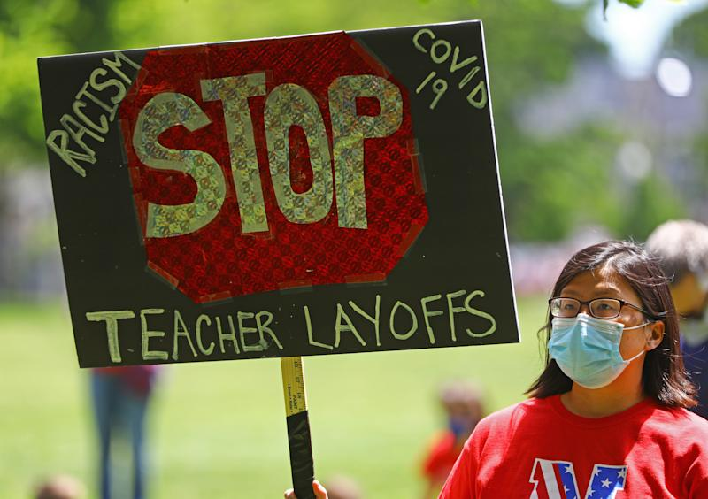 BROOKLINE, MA - JUNE 1: Melissa Smith, the parent of a 2019 high school graduate, holds a sign at a demonstration led by four Brookline High School juniors, students, teachers, and parents protesting the layoffs of over 300 Brookline Public Schools teachers in Brookline, MA on June 1, 2020. The group marched to Town Hall. (Photo by Pat Greenhouse/The Boston Globe via Getty Images)