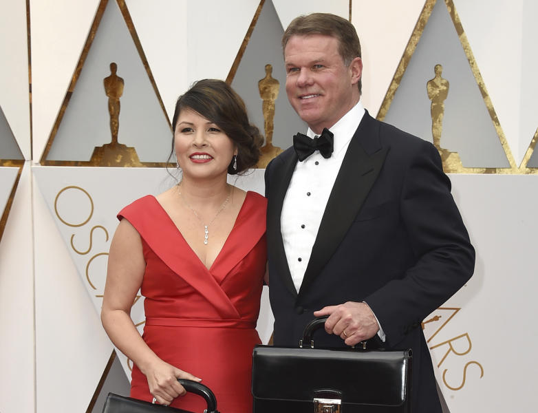 FILE - This Feb. 26, 2017 file photo shows Martha L. Ruiz, left, and Brian Cullinan from PricewaterhouseCoopers at the Oscars in Los Angeles. Film academy president Cheryl Boone Isaacs says the two accountants responsible for the best picture mistake will not work the Oscars again. Cullinan and Ruiz were responsible for the winners' envelopes at Sunday's Oscar show. Cullinan tweeted a photo of Emma Stone from backstage minutes before handing presenters Warren Beatty and Faye Dunaway the wrong envelope for best picture. Boone Isaacs said Cullinan's distraction caused the error. (Photo by Jordan Strauss/Invision/AP, File)