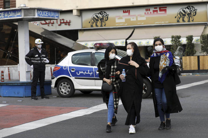 Image: A policeman and pedestrians wear masks to help guard against the Coronavirus, in downtown Tehran, Iran