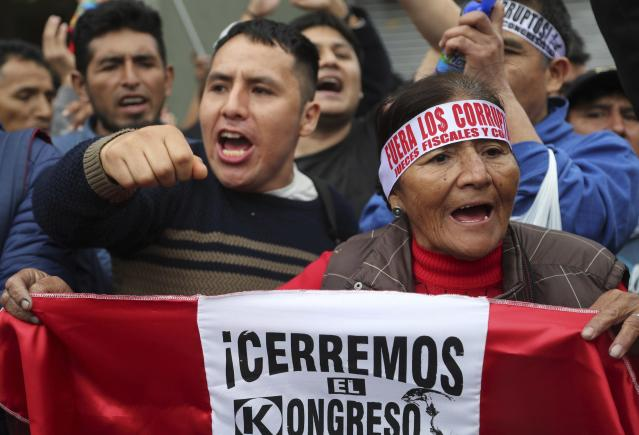 "A demonstrator holds up the Spanish message ""Close the congress"" during a protest against lawmakers who are pushing forward a vote to select an almost-full slate of new magistrates to the Constitutional Tribunal, in Lima, Peru, Monday, Sept. 30, 2019. Lawmakers are pushing forward the vote despite President Martín Vizcarra's warning the move threatens his fight against corruption and that he'll dissolve the opposition-controlled legislature. (AP Photo/Martin Mejia)"