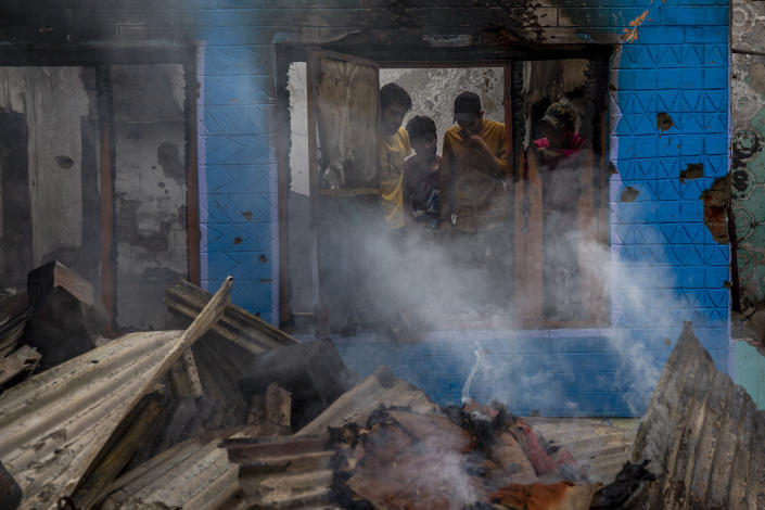 Smoke rises from the debris of a house destroyed in a gunfight in Pulwama, south of Srinagar, Indian controlled Kashmir, Wednesday, July 14, 2021. Three suspected rebels were killed in a gunfight in Indian-controlled Kashmir on Wednesday, officials said, as violence in the disputed region increased in recent weeks. Two residential houses were also destroyed. (AP Photo/ Dar Yasin)