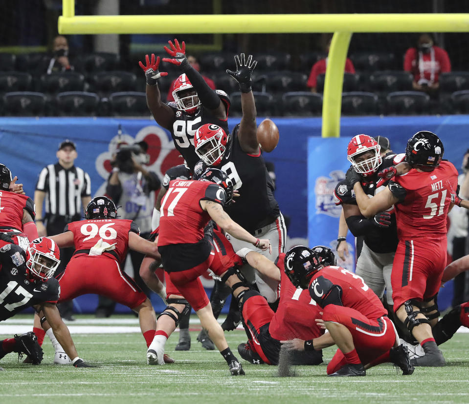 Georgia defensive lineman Jordan Davis, center, blocks the Cincinnati field goal attempt by Cole Smith (17) during the first half in the NCAA college football Peach Bowl game on Friday, Jan. 1, 2021, in Atlanta. (Curtis Compton/Atlanta Journal-Constitution via AP)