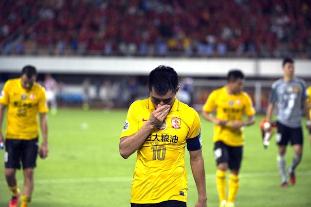 Zheng Zhi (C), team captain of China's Guangzhou Evergrande and his teammates walk off the pitch after losing to Australia's Western Sydney Wanderers in Guangzhou on August 27, 2014 (AFP Photo/)