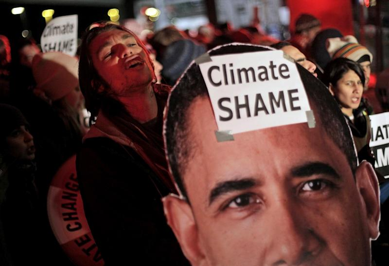 FILE - In this Dec. 19, 2009 file photo, demonstrators hold a picture of President Barack Obama and signs during a demonstration outside the Bella Center, the venue of the U.N. Climate Conference in Copenhagen, Denmark. A federal appeals court on Tuesday upheld the first-ever regulations aimed at reducing the gases blamed for global warming. (AP Photo/Peter Dejong, File)