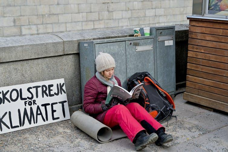Greta Thunberg sits reading with her famous sign nearby.
