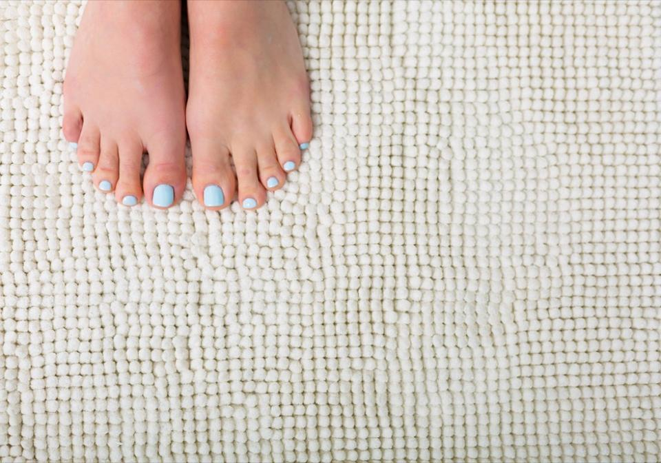 woman's feet on white bathroom rug, interior design mistakes