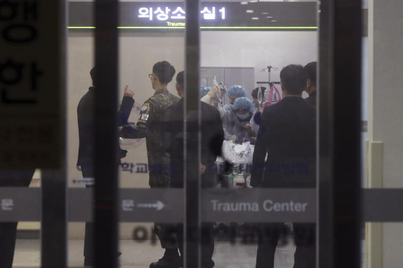 In this Monday, Nov. 13, 2017, file photo, a South Korean army soldier, second from left, is seen as medical members treat an unidentified injured person, believed to be a North Korean soldier, at a hospital in Suwon, South Korea. North Korean soldiers shot at and wounded a fellow soldier who was crossing a jointly controlled area at the heavily guarded border to defect to South Korea on Monday, the South's military said. (Hong Ki-won/Yonhap via AP, File)