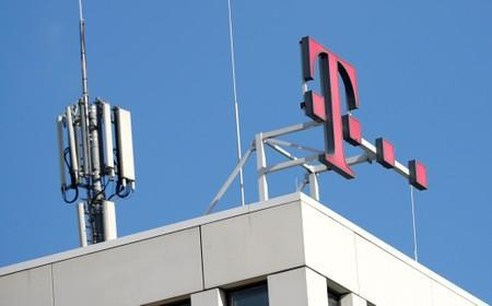 FILE PHOTO: GSM mobile phone antennas and the logo of Deutsche Telekom AG are seen atop of the headquarters of German telecommunications giant in Bonn