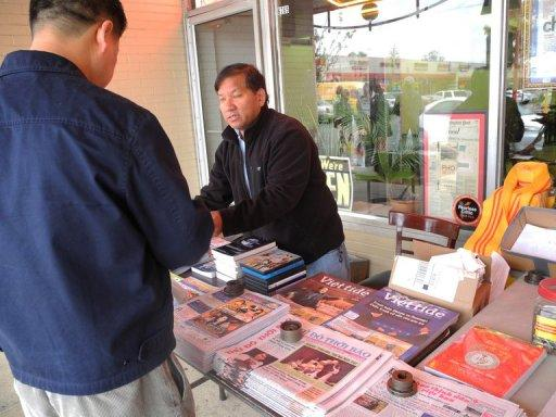 Newspaper vendor Tony Nguyen serves a customer at a table full of Vietnamese-language publications about the US election at the Eden Center shopping complex in the Washington suburb of Falls Church, Virginia, on October 28, 2012. The campaigns of both President Barack Obama and Republican Mitt Romney have been reaching out to Asian Americans, who form the fastest growing US racial group