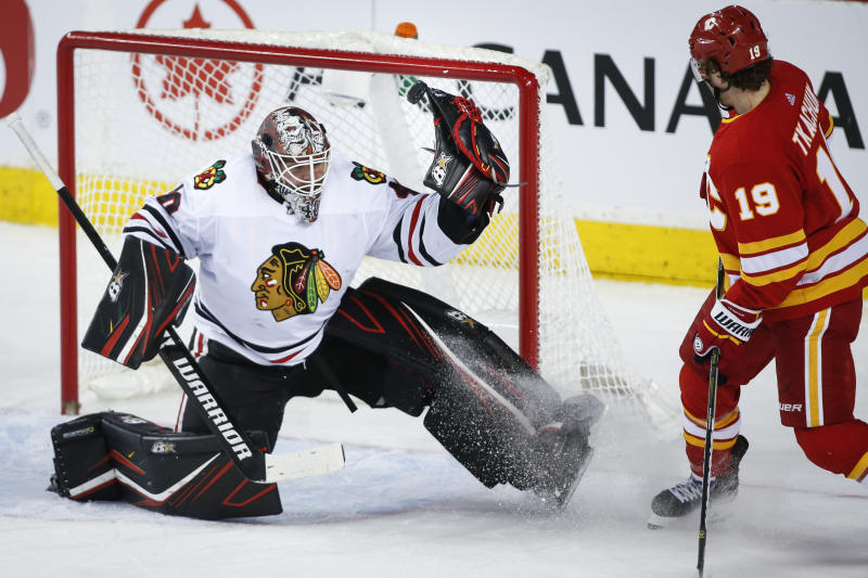 Chicago Blackhawks goalie Robin Lehner, left, manages to tip the puck away as Calgary Flames' Matthew Tkachuk watches during the second period of an NHL hockey game Tuesday, Dec. 31, 2019, in Calgary, Alberta. (Jeff McIntosh/The Canadian Press via AP)