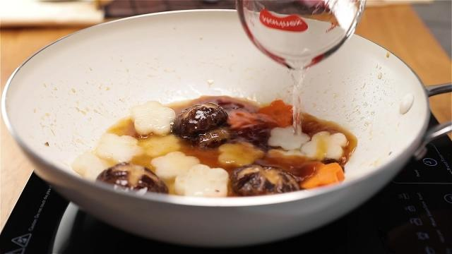 Adding water to frying pan to braise vegetables