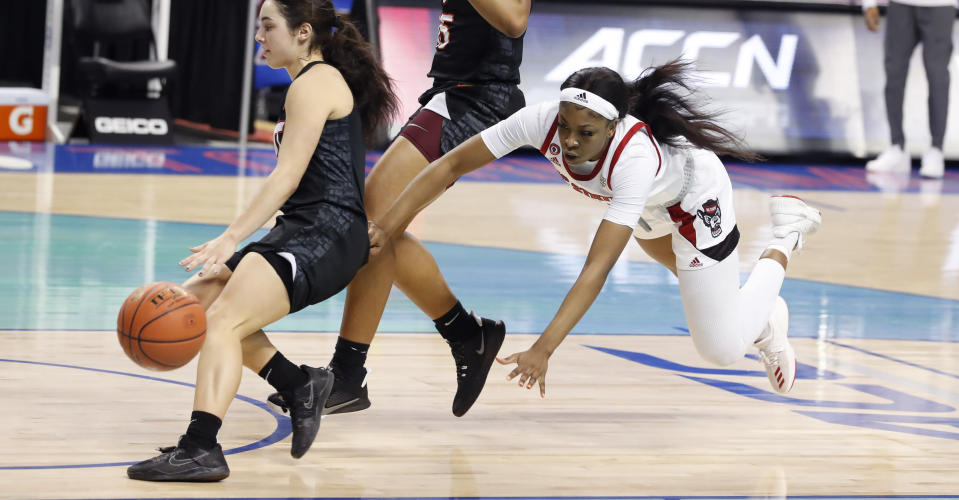North Carolina State's Jada Boyd (5) dives after running down the court with the ball, behind Virginia Tech's Georgia Amoore (5) during the first half of an NCAA college basketball game in the Atlantic Coast Conference women's tournament in Greensboro, N.C., Friday, March 5, 2021. (Ethan Hyman/The News & Observer via AP)