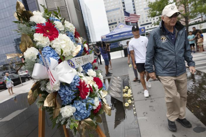 People file past a wreath in memory of Marine Sgt. Johanny Rosario Pichardo, from Lawrence, Mass., after placing a rose at the Massachusetts Fallen Heroes Memorial, Saturday, Aug. 28, 2021, in Boston. The 13 roses are in memory of the U.S. service members killed in a suicide bombing at the airport in Kabul, Afghanistan, including Rosario. (AP Photo/Michael Dwyer)