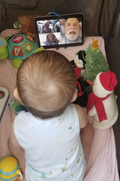 In this March 23, 2020, photo provided by Julie Bufkin, her 7-month-old boy, Calvin, interacts with his grandparents, Debbie and Allan Cameron, in Chandler, Ariz., on a FaceTime video call from his crib in Tempe, Ariz. The Camerons are among the grandparents all over the country going through a piercing distance from their loved ones for their own protection during the coronavirus crisis. (Julie Bufkin via AP)