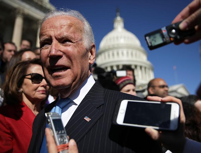 Joe Biden speak to journalists at a protest against the dismantling of Obamacare: Getty Images