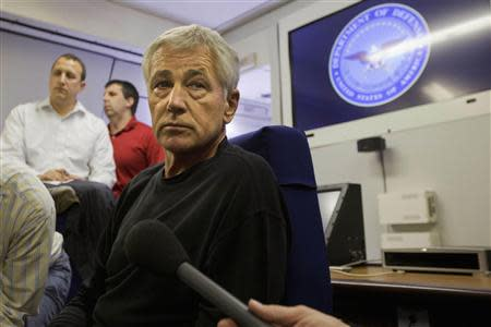 U.S. Defense Secretary Chuck Hagel turns to listen to a question from the travelling press aboard a U.S. military aircraft plane en route to Seoul