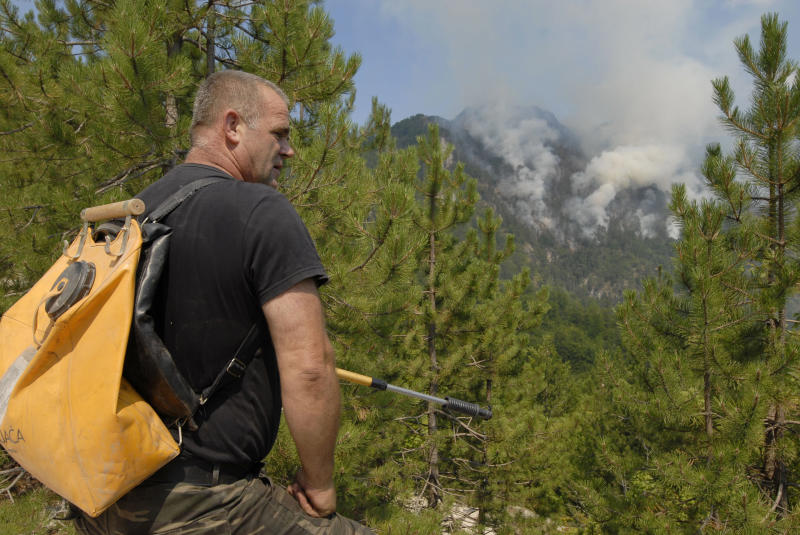 Bosnian fire fighter Ibro Alibasic looks at the raging wildfires near the Bosnian town of Konjic, 40 kms south of Sarajevo, Bosnia on Thursday, Aug 9, 2012. As firefighters tried to contain two wildfires near an ammunition factory in southern Bosnia on Thursday, one of the blazes began setting off explosions in a minefield left over from the country's war in the 1990s, officials said. (AP Photo/Sulejman Omerbasic)