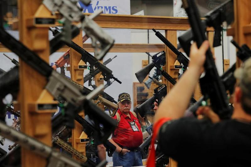 Gun enthusiasts look at rifles during the annual National Rifle Association (NRA) convention in Dallas, Texas.