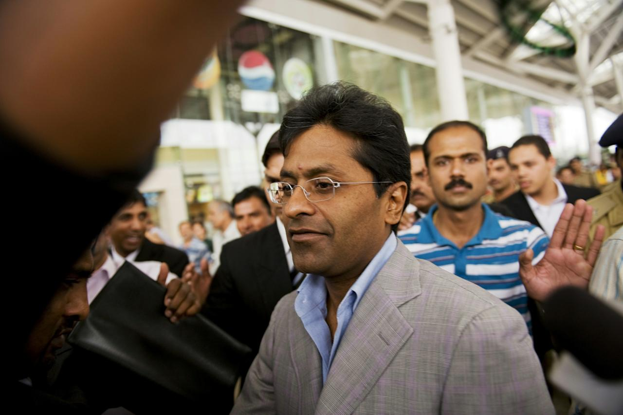 TO GO WITH Cricket-T20-IND-India-IPL FOCUS by Kuldip Lal (FILES) In this file picture taken on April 28, 2010, suspended Indian Premier League (IPL) Chairman Lalit Modi (C) arrives at Indira Gandhi International Airport's domestic terminal in New Delhi.   Lalit Modi, the Indian Premier League (IPL) cricket founder, was thrown out of the BCCI following allegations of corruption, indiscipline and money-laundering, all of which he denies. Modi, who has not been seen in India since IPL 3 ended in April, is also facing a government probe for financial irregularities and could have his passport revoked. AFP PHOTO/Manpreet ROMANA/FILES (Photo credit should read MANPREET ROMANA/AFP/Getty Images)