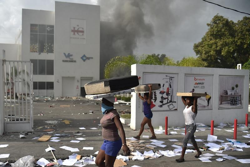 People carry loot from a shop in the commune of Petionville during protests against an increase in fuel prices, which the government has suspended (AFP Photo/HECTOR RETAMAL)
