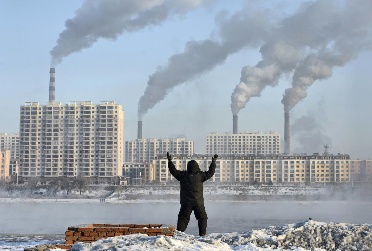 """A man exercises in the morning as he faces chimneys emitting smoke behind buildings across the Songhua river in Jilin in this February 24, 2013 file photo. China will """"declare war"""" on pollution, Premier Li Keqiang said on March 5, 2014 as the country began its annual meeting of parliament. Picture taken February 24, 2013. REUTERS/Stringer/Files (CHINA - Tags: ENVIRONMENT BUSINESS POLITICS) CHINA OUT. NO COMMERCIAL OR EDITORIAL SALES IN CHINA"""