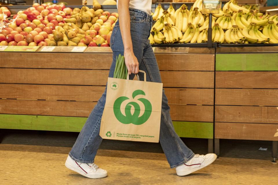 A Woolworths shopper carries a paper bag.