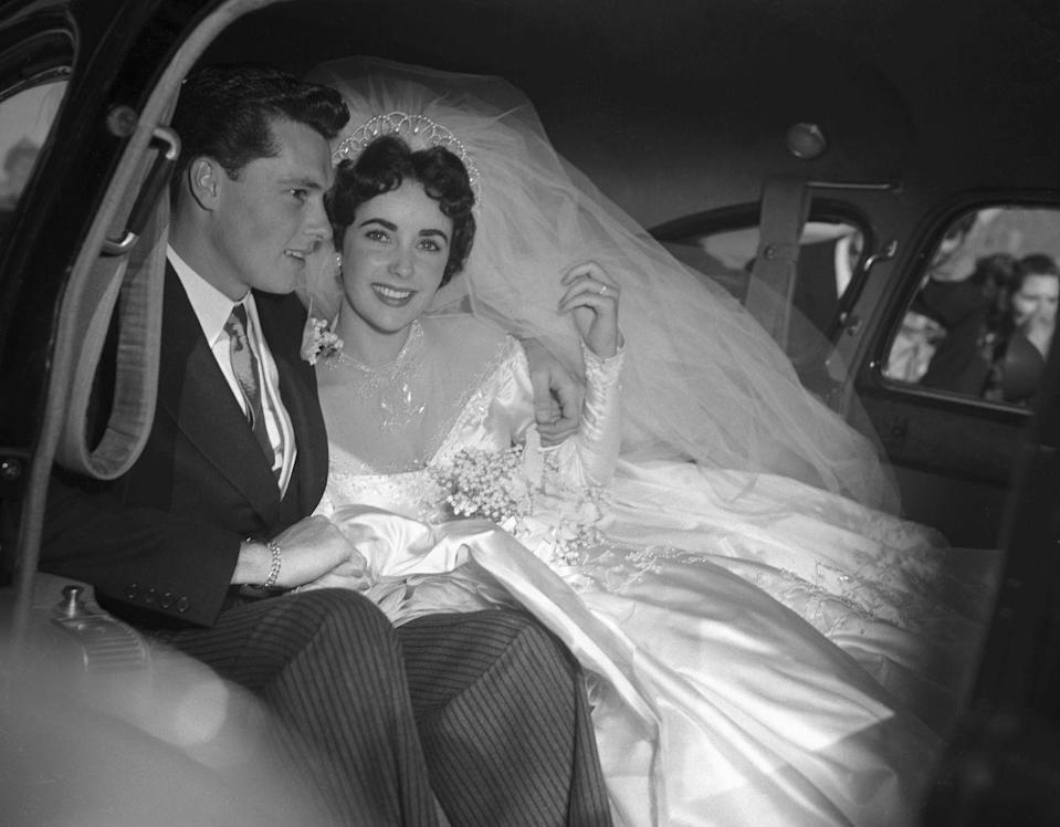 """<p>Actress Elizabeth Taylor and hotel heir Conrad """"Nickie"""" Hilton, Jr. pose in the limousine as they head to their wedding reception at the Bel-Air Country Club in 1950. The couple stayed married for just eight months. Taylor went on to remarry six more times. Hilton only married once more–to Patricia McClintock, from 1958–1965–whom he divorced just a few years before his death.<br></p>"""
